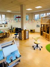 Schmetterlingsraum mit Kreativbereich, Spielteppich und einen Bereich zum ausruhen